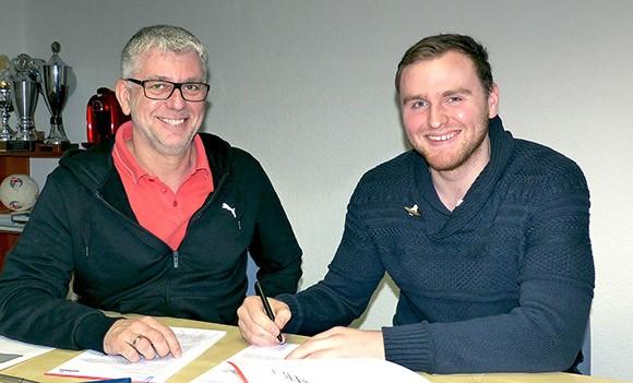 Torwart Lucas Puhl bei der Unterschrift, links Geschäftsführer Frank Böcking. (Foto: TuS Ferndorf)
